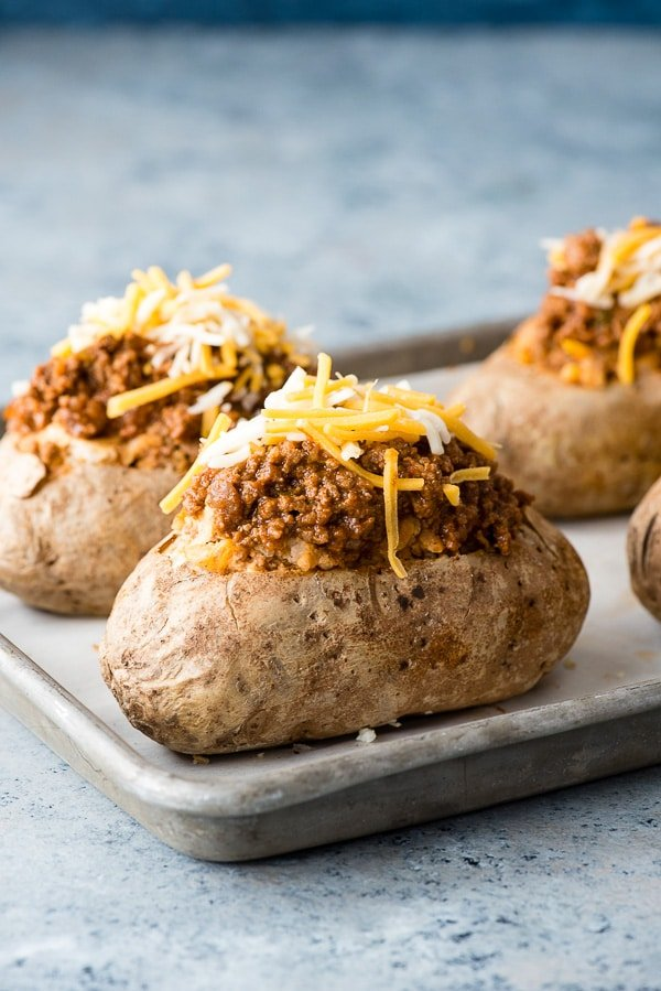 Taco-Stuffed Baked Potatoes recipe. Spicy, ground beef mixed with cheesy sour cream mashed potatoes for a taco-inspired comfort food main dish recipe! Gluten-free.- BoulderLocavore.com
