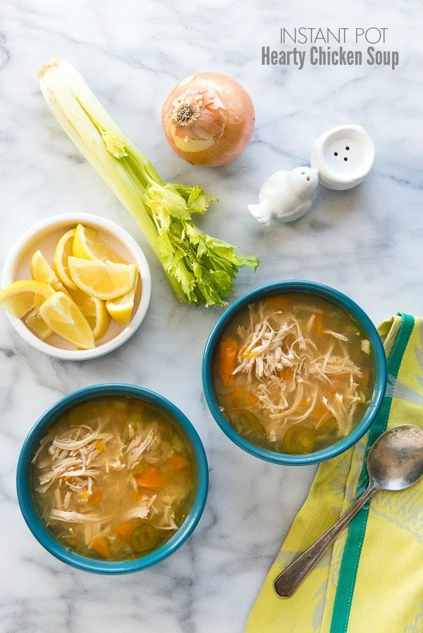 Two blue bowls of hearty chicken soup with a bowl of lemon wedges, fresh celery stalks, and onion and green napkin
