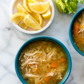 Instant Pot Hearty Chicken Soup in a blue bowl with lemon wedges from above