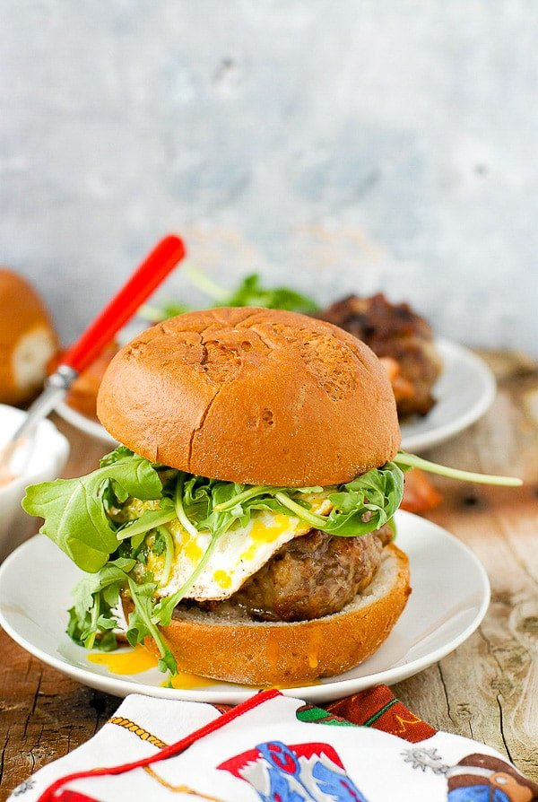 Hot, juicy Bacon-and-Egg Cheese Breakfast Burger with arugula on a white plate BoulderLocavore.com