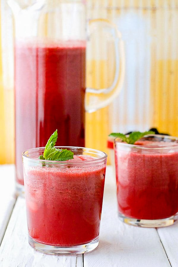Blackberry Mint Agua Fresca in a glass pitcher with fresh mint
