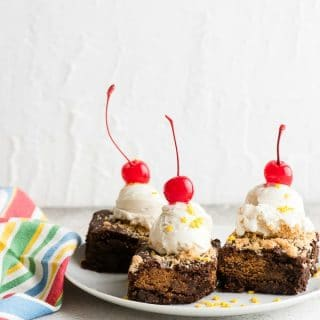 Freshly baked Chocolate Chip Cookie Stuffed Brownies with a scoop of vanilla ice cream and cherries on a white plate with striped napkin (allergy-friendly, gluten-free) BoulderLocavore.com
