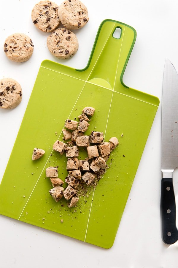 Gluten-free chocolate chip cookies chopped on a green cutting board
