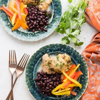 Juicy, fast-to-cook Chili Lime Chicken with sides dishes on green plates with copper silverware Boulderlocavore.com