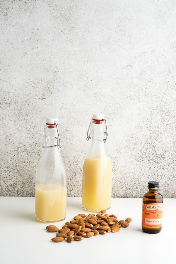 Homemade orgeat syrup in vintage bottles with almonds and orange blossom water BoulderLocavore.com