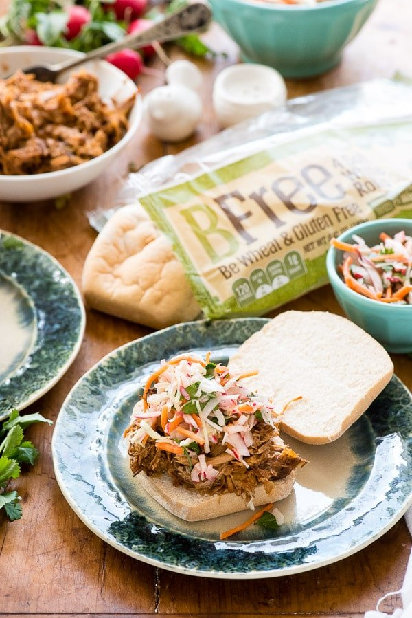 Slow cooker pulled pork sandwiches with radish slaw, gluten-free white rolls on a green plate BoulderLocavore.com
