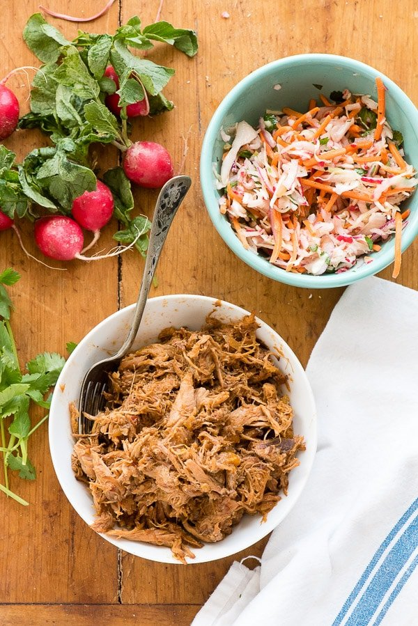 Slow cooker shredded pulled pork and radish slaw, fresh radishes and a white kitchen towel with blue stripe BoulderLocavore.com