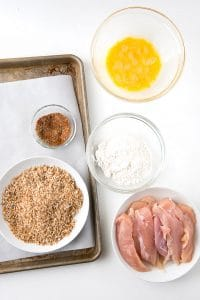 Homemade gluten-free breadcrumbs, homemade taco seasoning, chicken tenderloins, gluten-free flour, whisked eggs with a rimmed baking sheet lined with parchment paper BoulderLocavore.com