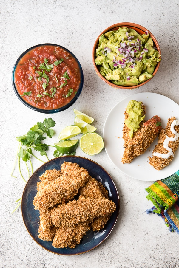 Crisp, homemade baked gluten-free Taco Chicken Tenders on a blue plate with salsa, guacamole, creama, cilantro and lime wedges BoulderLocavore.com