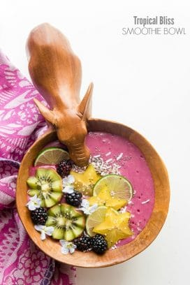 Fresh, healthy Tropical Bliss Smoothie Bowl with kiwi, blackberries, coconut, star fruit, hemp seed, chia seed topping in a carved elephant bowl BoulderLocavore.com