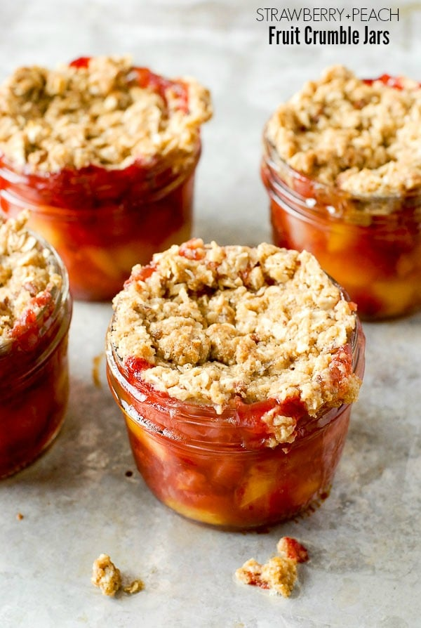 Freshly baked strawberry and peach Fruit Crumble Jars on metal surface