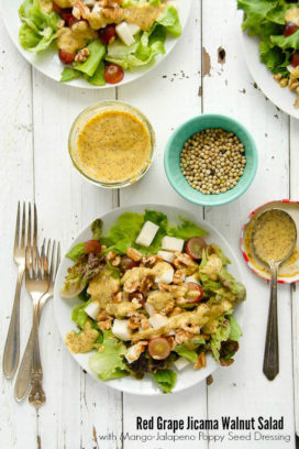 Fresh and crunchy Red Grape Jicama Walnut Salad with Mango-Jalapeno Poppy Seed Dressing on a white plate and vintage painted fence boards BoulderLocavore.com