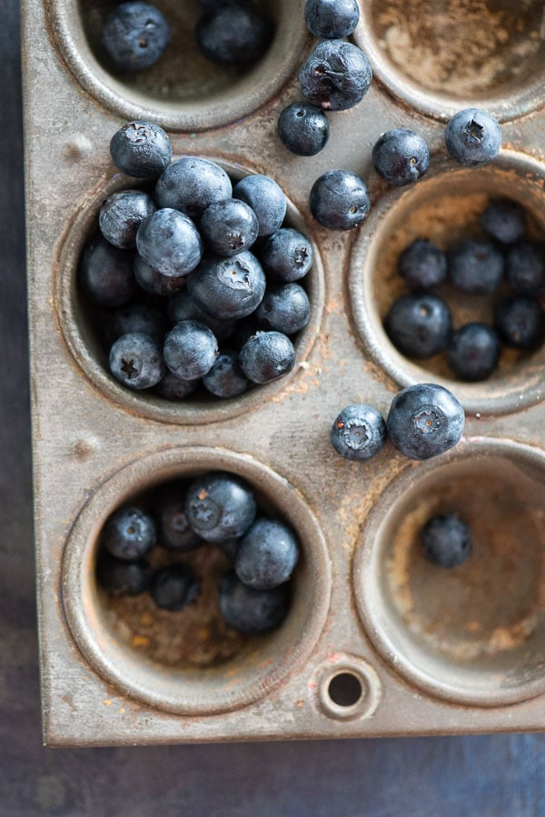 Fresh blueberries in a distressed vintage muffin tin