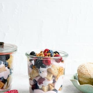 Easy for breakfast or a snack Overnight Lemon Muffin Breakfast Trifles are packed with strawberry yogurt, fresh strawberries and blueberries in a pint Weck jars with red and blue spoons BoulderLocavore.com