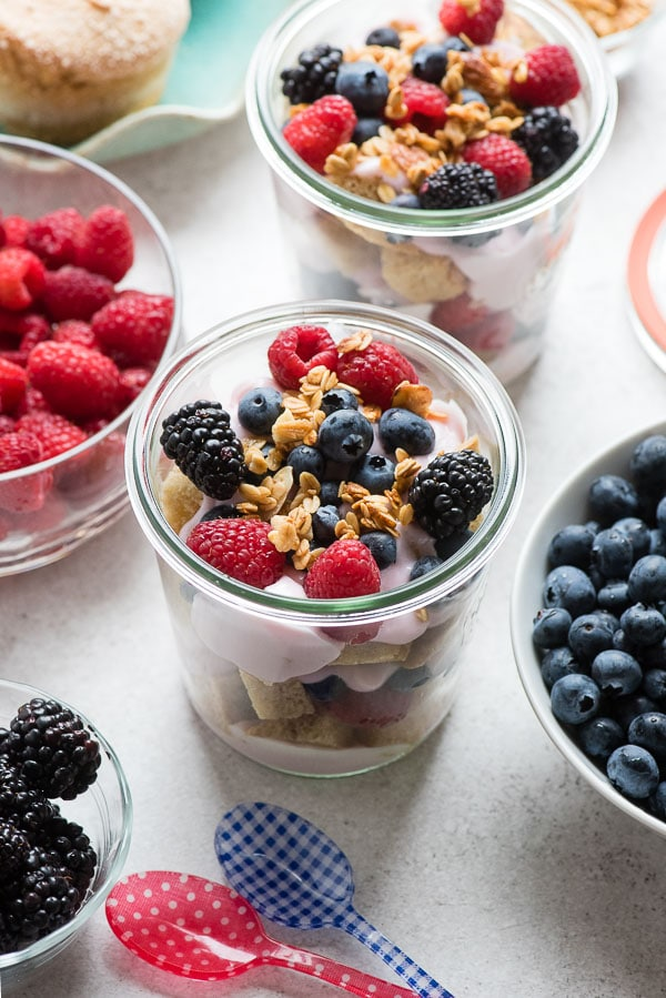 Glass jars of gluten-free Overnight Lemon Muffin Breakfast Trifles with fresh raspberries, blueberries