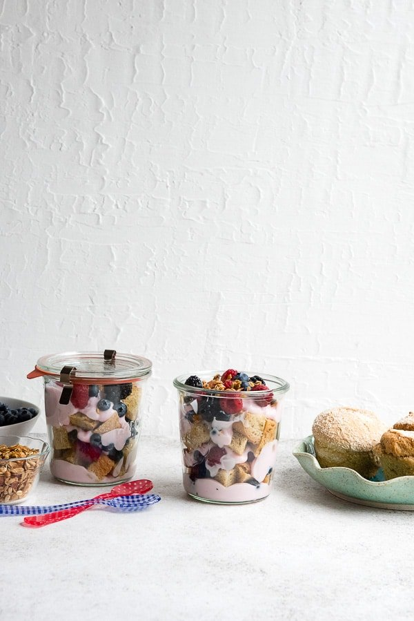 Glass pint Weck jars full of Overnight Lemon Muffin Breakfast Trifles with gluten-free lemon muffins, fresh berries and strawberry yogurt with granola on top! BoulderLocavore.com