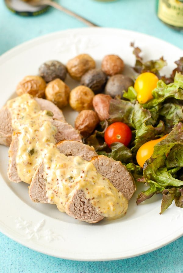 Slices of Pork Tenderloin with Mustard Caper Cream Sauce, fresh salad and roasted potatoes on a vintage ironstone plate BoulderLocavore.com