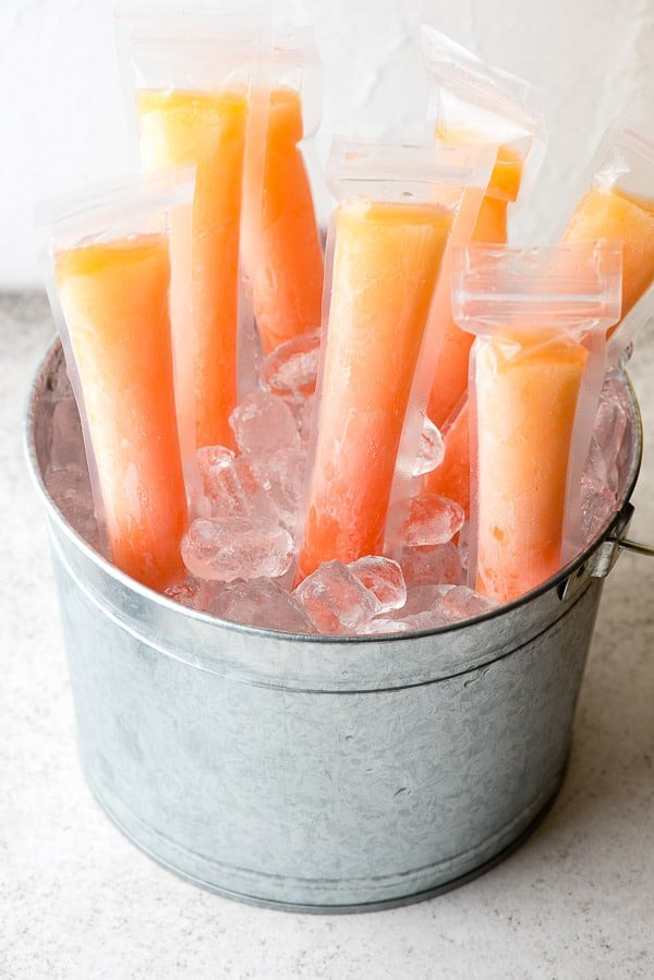 Orange and pink frozen Tequila Sunrise Freezer Pops for adults in a silver galvanized bucket of ice BoulderLocavore.com