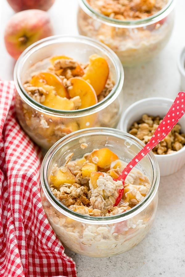 Single serving Peach Pie Overnight Oats with fresh summer peaches, chopped walnuts and brown sugar with a red and white checked towel BoulderLocavore.com