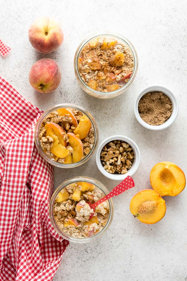 Individual servings of gluten-free Peach Pie Overnight Oats in glass jars with sliced peaches, chopped walnuts, brown sugar with a red acrylic Sabre French spoon and red and white checked kitchen towel BoulderLocavore.com