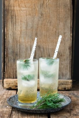 Pine Whiskey Cooler cocktail in a tall glass with ice and pine sprig - 16 Best Summer Cocktails BoulderLocavore.com