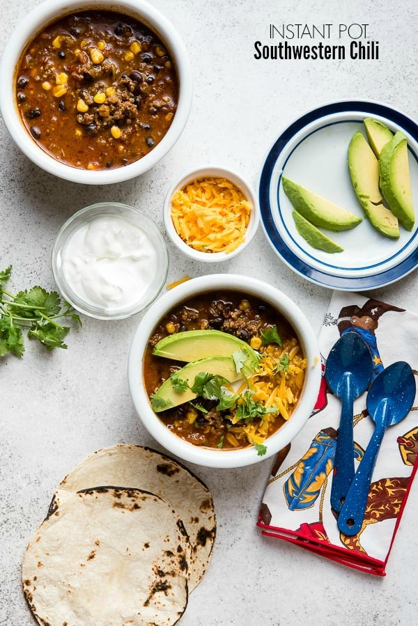 Savory Instant Pot Southwest Chili in a white bowl with fresh cilantro, avocado slices, grated cheddar cheese and sour cream BoulderLocavore.com