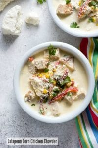White bowl of Jalapeno Corn Chicken Chowder soup with cojito cheese and chopped cilantro