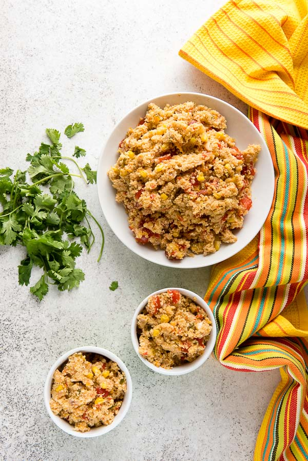 Three bowls of spicy Mexican Fiesta Cauliflower Rice with fresh cilantro and yellow Mexican kitchen towel | BoulderLocavore.com