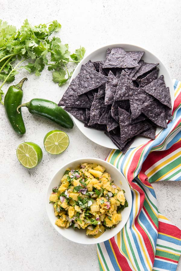 Roasted Pineapple Salsa in white bowl with blue corn tortilla chips, sliced limes, cilantro and jalapeno peppers BoulderLocavore.com