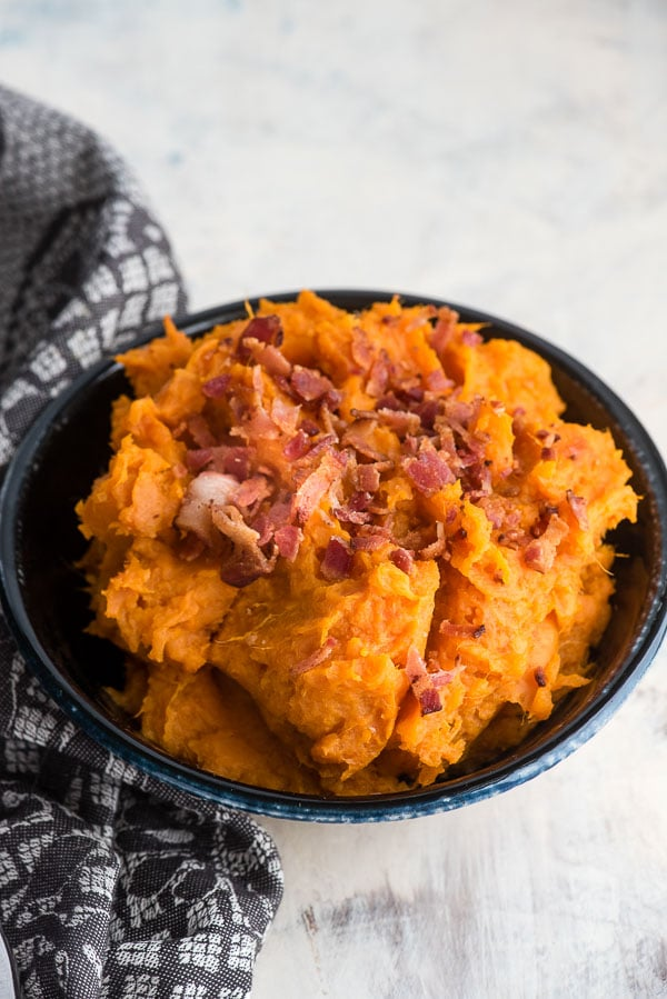 Creamy bowl of Instant Pot Mashed Chipotle Sweet Potatoes in a black glazed bowl with gray kitchen towel BoulderLocavore.com