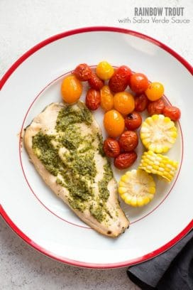 Rainbow Trout with Salsa Verde Sauce, blistered cherry tomatoes and fresh corn wheels on a white enamel plate with red trim BoulderLocavore.com
