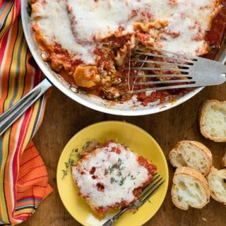 Spicy Sausage Skillet Lasagna with melted cheese top, single serving on small yellow plate with sliced gluten-free baguette BoulderLocavore.com