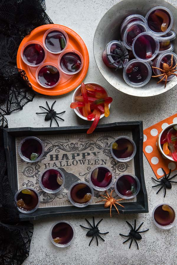 Spooky Halloween Squirm Jello shots with gummy worms inside on a Halloween serving tray, with spiders BoulderLocavore.com