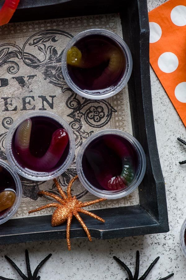Halloween grape Squirm Jello Shots with gummy worms in small snack containers with spiders BoulderLocavore.com