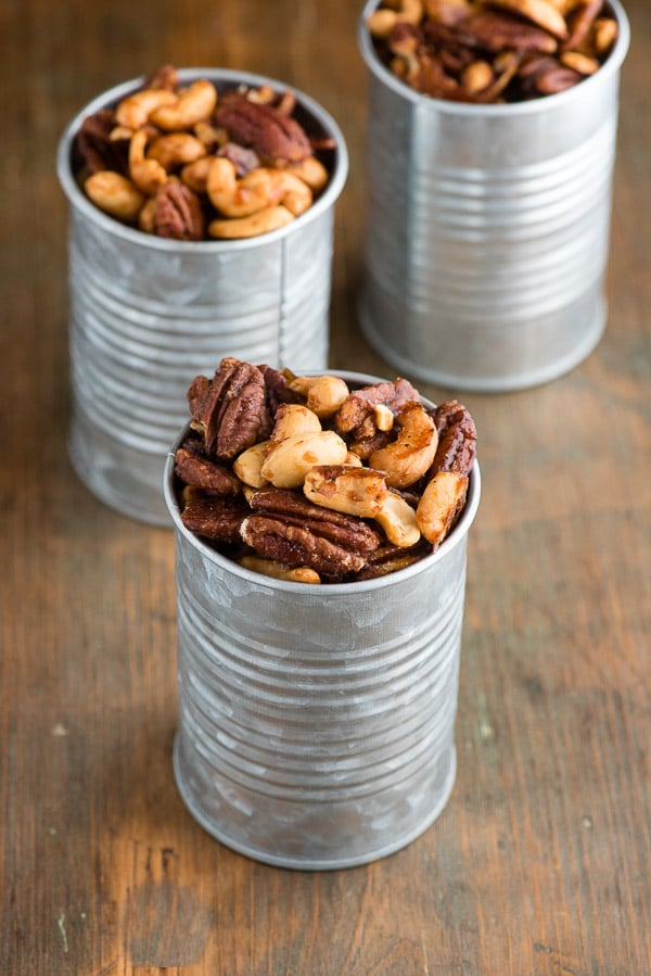 Sweet Spiced Nuts are candied cashews and pecans that are spicy and sweet, in galvanized cans on a dark wood antique bread board BoulderLocavore.com