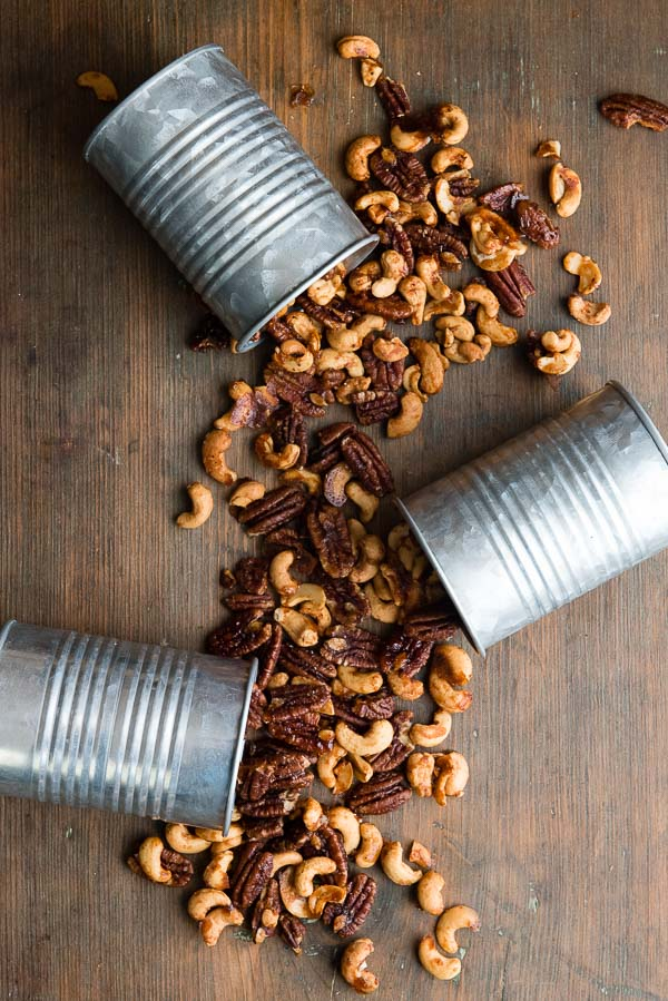 Three galvanized cans tipped over spilling Sweet Spiced Nuts over a dark wood antique bread board BoulderLocavore.com
