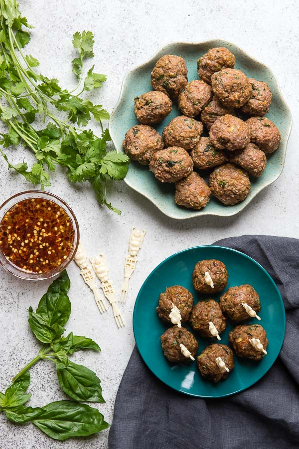 Two blue plates of gluten-free Thai Chicken Meatballs with fresh Sweet-Spicy Dipping Sauce, fresh cilantro and basil BoulderLocavore.com