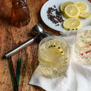 Glasgow Hot Toddy with clove-studded lemon slice in Waterford crystal etched glasses with a handled jigger