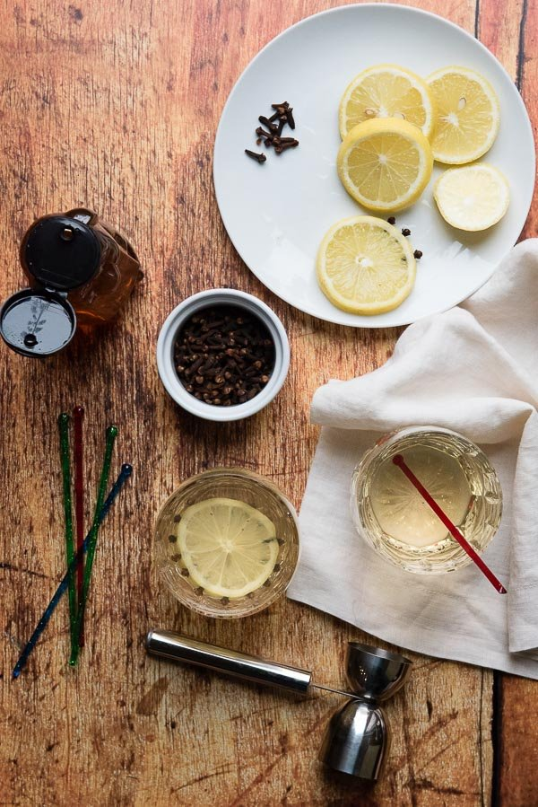 Glasgow Hot Toddy with cloves, lemon slice, colorful stirring sticks and cream colored linen napkin BoulderLocavore.com