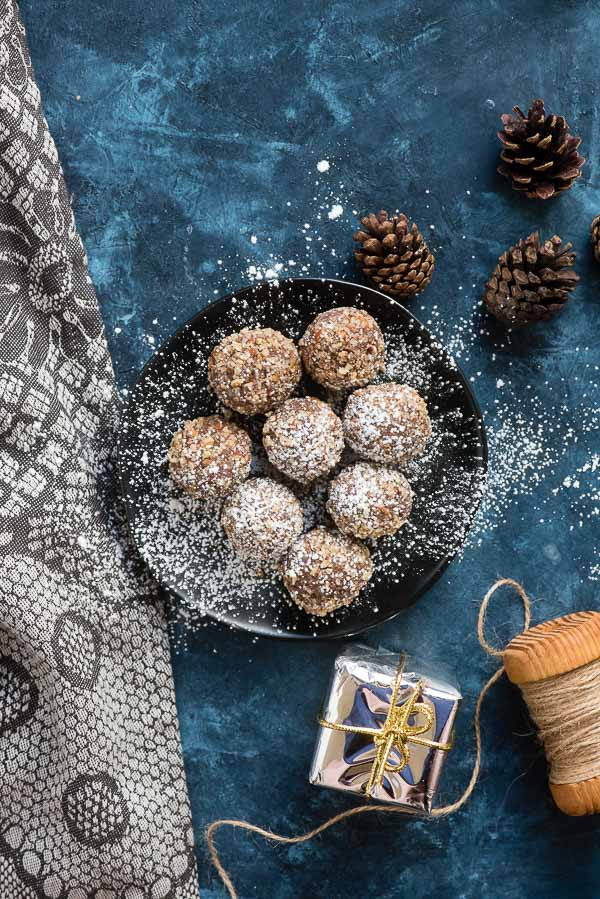 No Bake Pecan Rum Balls with powdered sugar on a black plate with gray kitchen towel BoulderLocavore.com