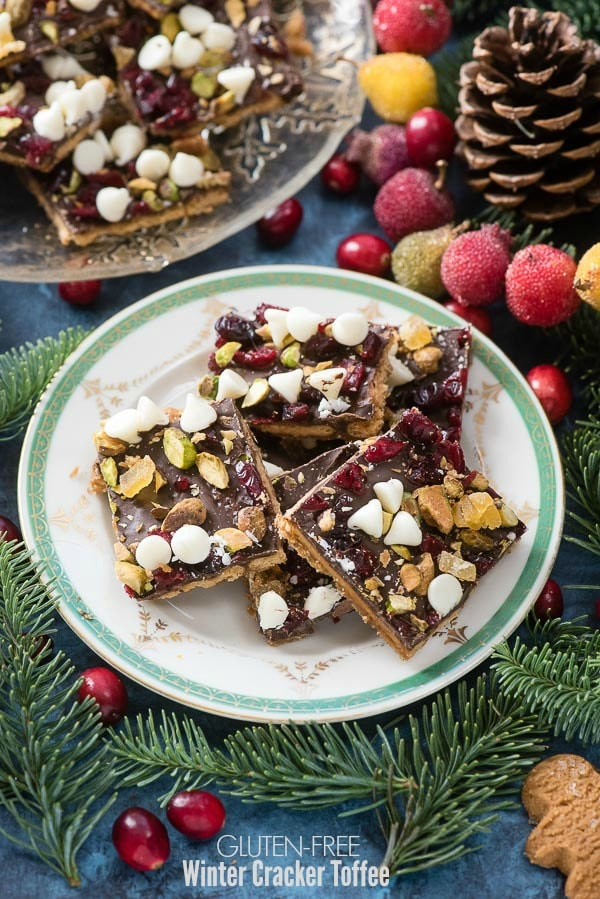 Gluten-Free Winter Cracker Toffee with cranberries, white chocolate chips, pistachio nuts, candied ginger and sea salt on a gold rimmed plate BoulderLocavore.com