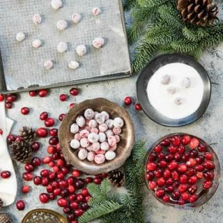 fresh and sugared cranberries in a silver bowl and on a baking sheet
