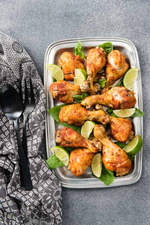 A pewter platter of Instant Pot Smoked Paprika & Garlic Chicken Legs with lime wedges, black serving utensils and gray kitchen towel