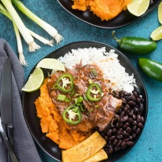 Slow Cooker Caribbean Pot Roast with sweet potatoes, rice, black beans and plantains on a black plate with deep ocean blue surface BoulderLocavore.com
