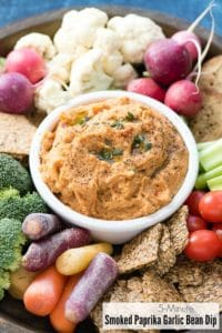 5-Minute Smoked Paprika Garlic Bean Dip in a white bowl with cut vegetables and crackers