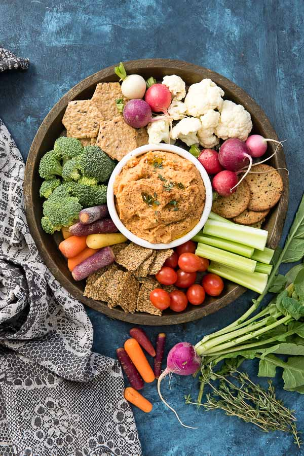 5-Minute Smoked Paprika Garlic Bean Dip with fresh vegetables and gluten-free cracker s on a bronze tray