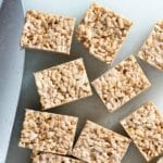 Gluten-free Brown Butter Rice Cereal Treat squares on a white cutting board with knife