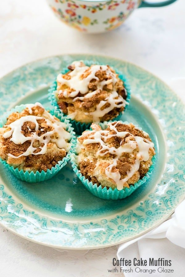 Three Coffee Cake Muffins with fresh orange glaze on a blue plate with flowered coffee cup