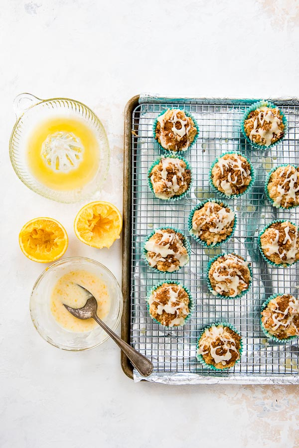 Baking sheet of coffee cake muffins with bowl of orange glaze and spoon