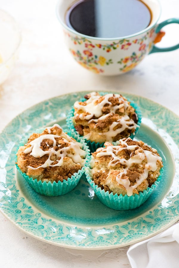 Three freshly baked gluten-free Coffee Cake Muffins with orange glaze on a blue embossed plate